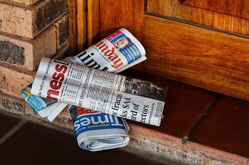 Newspaper by wooden door